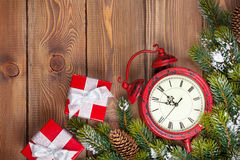 Christmas wooden background with clock, gift boxes and snow fir Stock Photos