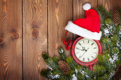 Christmas wooden background with clock and snow fir tree Royalty Free Stock Image
