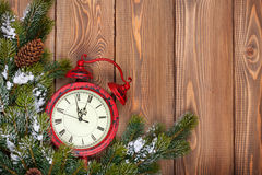 Christmas wooden background with clock and snow fir tree Stock Images