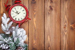 Christmas wooden background with clock, snow fir tree Stock Photos