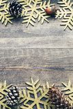 Christmas wooden background with decorative snowflakes and pine cones. Stock Images