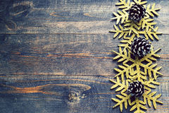 Christmas wooden background with decorative snowflakes and pine cones. Royalty Free Stock Photography