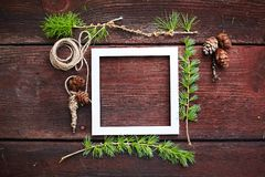 Christmas wooden background. Fir branches and cones with white frame for copyspace. Royalty Free Stock Images