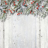 Christmas wooden background with fir branches and holly. Christmas vintage background with fir branches,holly, snow and cool Christmas decorations on the wooden Royalty Free Stock Images