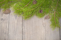 Christmas wooden background with fir branches and pine cones Royalty Free Stock Image