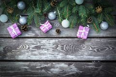 Christmas holiday background with gifts boxes with fir branches, pine cones, christmas balls on wooden table. Flat lay, top view w stock photography