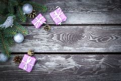 Christmas holiday background with gifts boxes with fir branches, pine cones, christmas balls on wooden table. Flat lay, top view w stock image