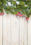 Christmas wooden background with fir tree and holly berry Royalty Free Stock Photography