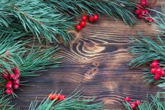Christmas wooden background with pine branches, red berries, cop Stock Photography