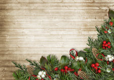 Christmas wooden background with poinsettia, holly and fir branc. Christmas wood background with vintage postcard with Christmas decorations made of branches Royalty Free Stock Photo