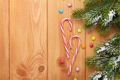 Christmas wooden background with snow fir tree and candies Royalty Free Stock Photos