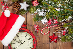 Christmas wooden background with snow fir tree, decor and clock Stock Photography