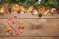 Christmas wooden background with snow fir tree, spices, gingerbr Stock Photos