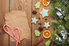 Christmas wooden background with snow fir tree, spices, gingerbr Stock Photography