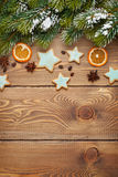 Christmas wooden background with snow fir tree, spices, gingerbr Royalty Free Stock Photos