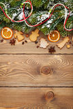 Christmas wooden background with snow fir tree, spices, gingerbr Royalty Free Stock Image