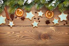 Christmas wooden background with snow fir tree, spices, gingerbr Stock Image
