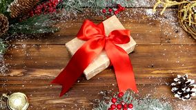 Christmas wooden background with snowy branch Top view. a gift with a red bow on a wooden table stock video