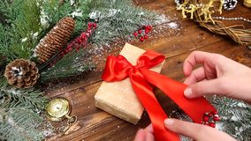 Christmas wooden background with snowy branch Top view. The hands of a young girl put a gift with a red bow on the table stock video