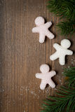 Christmas wooden background with sugar little men and fir branch Royalty Free Stock Images