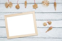 Christmas wooden decorations and photo frame on a white wooden background. royalty free stock images
