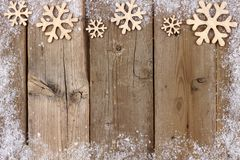 Christmas wooden snowflake top border with snow frame on wood Royalty Free Stock Photography