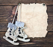 Christmas wooden toy figure skates and a piece of old paper Stock Images