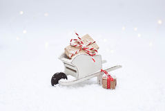 Christmas. Wooden wheelbarrow with Christmas gifts Stock Images