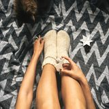 Christmas woolen socks on legs and woman holding stylish reindeer toy, and cute cat playing with holiday ornaments in festive. Room. Top view. Atmospheric cozy stock image