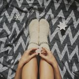 Christmas woolen socks on legs and woman holding stylish reindeer toy, relaxing on plaid with holiday ornaments in festive room. Top view. Atmospheric cozy royalty free stock image