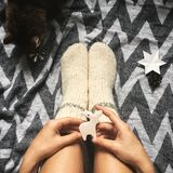 Christmas woolen socks on legs and woman holding stylish reindeer toy, and cute cat playing with holiday ornaments in festive. Room. Top view. Atmospheric cozy royalty free stock photography