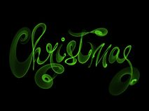 Christmas word lettering written with green fire flame or smoke on black background.  Stock Photos