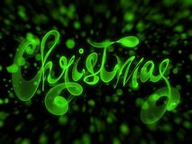Christmas word lettering written with green fire flame or smoke on blurred bokeh background.  Royalty Free Stock Photography