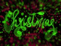Christmas word lettering written with green fire flame or smoke on blurred bokeh background.  Stock Photos