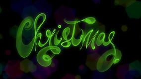 Christmas word lettering written with green fire flame or smoke on blurred bokeh background.  Stock Image