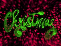 Christmas word lettering written with green fire flame or smoke on blurred bokeh background.  Stock Images