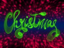 Christmas word lettering written with green fire flame or smoke on blurred bokeh background.  Royalty Free Stock Photo