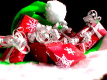 Christmas wrapped. Christmas gifts in red and white wrapping with ribbons and bows on a green Christmas hat Stock Images