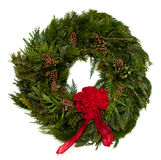 Christmas wreath. Green cedar Christmas wreath on isolated white background with red bow royalty free stock photography