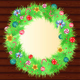 Christmas wreath with baubles and christmas tree. On wood background Royalty Free Stock Photo