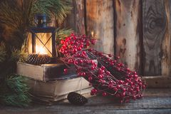 Christmas wreath with berries on old books with a lantern on wooden background. Christmas wreath on books with a lantern on the wooden background. Toned Royalty Free Stock Images