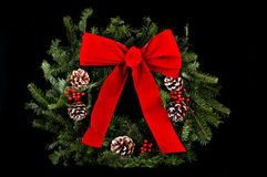Christmas Wreath on Black. A beautiful Christmas wreath with red bow, pine boughs, pine cones & red berries on a black background Stock Image