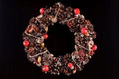 Christmas wreath on black pine wood. Stock Photos