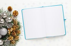 Christmas wreath and Blank open notepad on white background. New year goals concept, mockup, top view, copy space stock photos