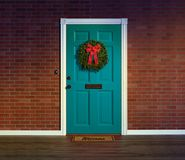 Christmas wreath on blue front door with welcome mat. stock photography