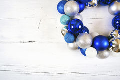 Christmas wreath of blue and white balls on wooden white surface. Royalty Free Stock Photography