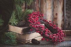 Christmas wreath on books on wooden background with branches of pine. Christmas wreath on books withbranches of pine on the wooden background stock photography