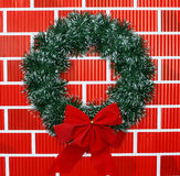 Christmas Wreath with Bow. Isolated on red brick wall background Stock Photos