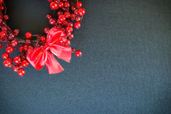 Christmas wreath and bow on a black canvas background. Christmas holiday wreath made of red berries and ribbon bow on a black canvas background with copy space Royalty Free Stock Image