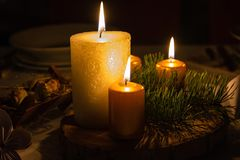 Christmas wreath with burning candles. Burning candles in christmas wreath in dark room royalty free stock photography